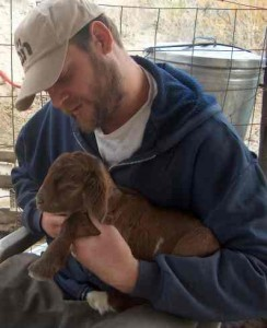 Man holding a young brown goat